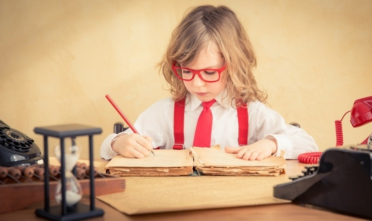 Child sitting counting money, writing in a notepad