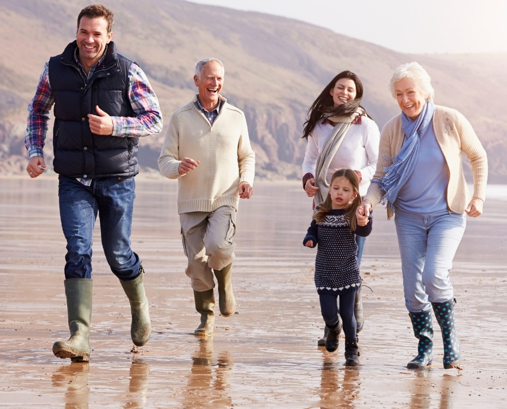 Multi Generational Family Running Across the Beach